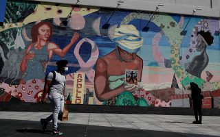A man wearing a protective face covering walks by a mural  in the Harlem neighborhood of New York City, New York, U.S., July 9, 2020. REUTERS/Shannon Stapleton     TPX IMAGES OF THE DAY