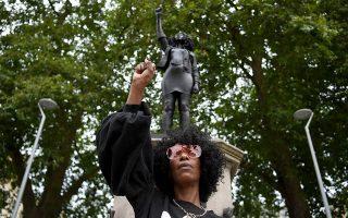 Τη θέση της αμφιλεγόμενης προσωπικότητας του 17ου αιώνα έλαβε η φιγούρα της Τζεν Ρέιντ, μίας μαύρης διαδηλώτριας που είχε φωτογραφηθεί με τη γροθιά υψωμένη, να στέκεται πάνω στη βάση του γκρεμισμένου αγάλματος. (Φωτ. EPA/NEIL HALL)