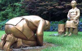 Το αμφιλεγόμενο γλυπτό του άνδρα που γονατίζει μπροστά σε θύμα σεξουαλικής εκμετάλλευσης, στον κορεατικό βοτανικό κήπο στην Πιονγκτσάνγκ. (Φωτ. REUTERS)