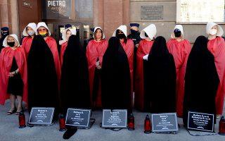 Μέλη πολωνικών γυναικείων οργανώσεων με νεκρολογίες γυναικών που έχουν πέσει θύματα ενδοοικογενειακής βίας, διαδηλώνουν στη Βαρσοβία. (Φωτ. A.P.)