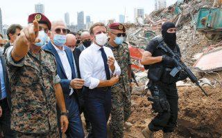 Ο Εμανουέλ Μακρόν χαιρετάει Λιβανέζους πολίτες, μέλη σωστικών συνεργείων, στο λιμάνι της Βηρυτού, πλάι στα ερείπια που άφησε πίσω της η τρομερή έκρηξη (φωτ. Thibault Camus / Pool via REUTERS).