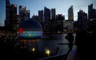 Τουρίστες φωτογραφίζουν το νέο εντυπωσιακό κτίριο με φόντο τους ουρανοξύστες των κολοσσών τραπεζών. Το νέο κτίριο- κατάστημα της Apple βρίσκεται μέσα στο νερό στο λιμάνι της Σιγκαπούρης.REUTERS/Edgar Su