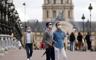 People wearing protective masks stand on the Alexandre III bridge as France reinforces mask-wearing as part of efforts to curb a resurgence of the coronavirus disease (COVID-19) across the country, in Paris, France August 28, 2020.    REUTERS/Charles Platiau