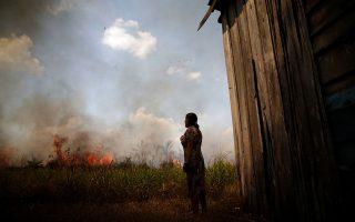 Η φωτιά πλησιάζει το σπίτι τους σε μια περιοχή του τροπικού δάσους του Αμαζονίου, κοντά στο Πόρτο Βέλχο. Φωτ. REUTERS