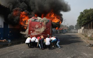 Demonstrators push a bus that was torched during clashes with the Bolivarian National Guard in Urena, Venezuela, near the border with Colombia, Saturday, Feb. 23, 2019. Venezuela's National Guard fired tear gas on residents clearing a barricaded border bridge between Venezuela and Colombia on Saturday, heightening tensions over blocked humanitarian aid that opposition leader Juan Guaido has vowed to bring into the country over objections from President Nicolas Maduro.(AP Photo/Rodrigo Abd)