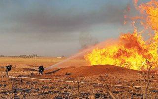 Πυροσβέστης ρίχνει νερό στη φωτιά που ξέσπασε μετά την έκρηξη σε αγωγό φυσικού αερίου βορειοδυτικώς της Δαμασκού. (Φωτ. REUTERS)