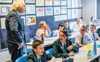 O Βρετανός πρωθυπουργός Μπόρις Τζόνσον κατά την επίσκεψή του στο σχολείο Castle Rock χθες, ημέρα έναρξης της νέας σχολικής χρονιάς. (Φωτ. REUTERS)