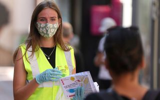 FILE PHOTO: A woman wearing a yellow vest hands out masks and information brochures where to wear mandatory masks in the busiest streets of the city, during the coronavirus disease (COVID-19) outbreak, in Amsterdam, Netherlands August 5, 2020. REUTERS/Eva Plevier/File Photo