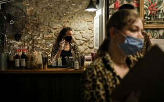 Staff members of a bar wear protective face masks, amid the spread of the coronavirus disease (COVID-19), in Athens, Greece, August 1, 2020. Picture taken August 1, 2020. REUTERS/Costas Baltas