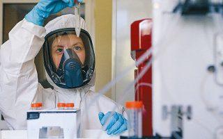 Yπάλληλος του ρωσικού Κέντρου Επιδημιολογίας και Μικροβιολογίας Gamelaya κρατάει στο χέρι το νέο εμβόλιο (φωτ. Α.Ρ.).