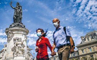 Φορώντας την υποχρεωτική, πλέον, προστατευτική μάσκα, ένα ζευγάρι περνάει δίπλα από το άγαλμα της Μαριάν στην πλατεία της Δημοκρατίας, στο Παρίσι (φωτ. EPA).