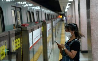 A woman wearing a face mask following the coronavirus disease (COVID-19) outbreak looks at her smartphone while waiting for a subway in Beijing, China August 11, 2020. REUTERS/Tingshu Wang