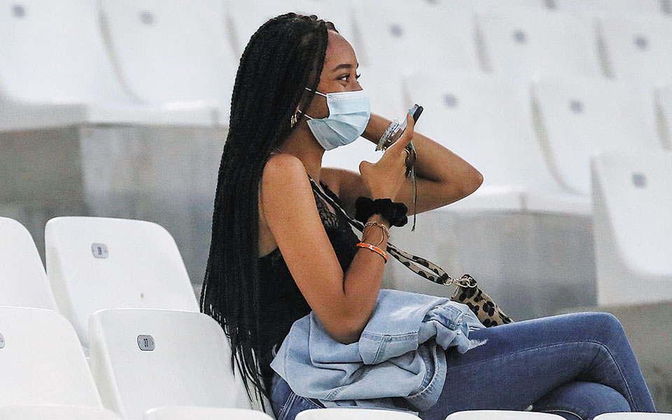 Mία φίλαθλος ανάμεσα σε δεκάδες άδεια καθίσματα, σε αγώνα ποδοσφαίρου στη Μασσαλία.