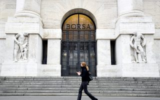 FILE PHOTO: A woman passes the Italian Stock Exchange in Milan, Italy, February 25, 2020. REUTERS/Flavio Lo Scalzo/File Photo