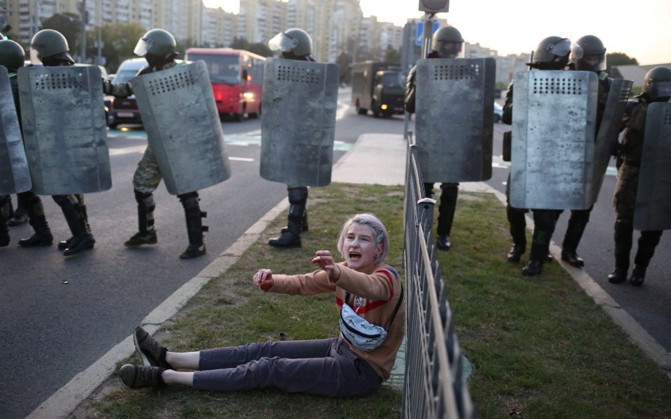 A woman reacts while sitting on the ground near Belarusian law enforcement officers, who disperse a crowd during a protest against the inauguration of President Alexander Lukashenko in Minsk, Belarus September 23, 2020. Tut.By via REUTERS  ATTENTION EDITORS - THIS IMAGE WAS PROVIDED BY A THIRD PARTY. MANDATORY CREDIT.