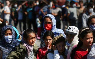 Πρόσφυγες και μετανάστες περιμένουν να παραλάβουν τρόφιμα και νερό από υπαλλήλους ΜΚΟ και εργολάβους με εντολή του υπουργείου Μεταναστευτικής Πολιτικής, κοντά στον κατεστραμμένο από πυρκαγιά καταυλισμό της Μόριας. (Φωτ. ΑΠΕ-ΜΠΕ/ΟΡΕΣΤΗΣ ΠΑΝΑΓΙΩΤΟΥ)
