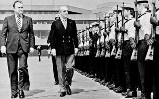 Τον Ελληνα πρωθυπουργό Κωνσταντίνο Καραμανλή υποδέχθηκε στο αεροδρόμιο ο Γερμανός αντικαγκελάριος και υπουργός Εξωτερικών Χανς-Ντίντριχ Γκένσερ, o οποίος στην προσφώνησή του χαιρέτισε την επιστροφή της Ελλάδας στη δημοκρατία. (Φωτ. ΙΔΡΥΜΑ «ΚΩΝΣΤΑΝΤΙΝΟΣ Γ. ΚΑΡΑΜΑΝΛΗΣ»)