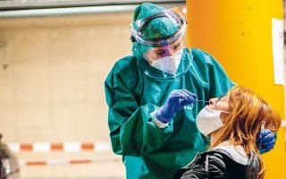 Υγειονομική υπάλληλος συλλέγει δείγμα για τεστ COVID-19 από μια γυναίκα, σε υπόγειο πάρκινγκ νοσοκομείου, στη Λιέγη του Βελγίου (φωτ. Reuters).