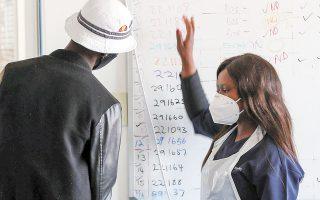 Yγειονομική υπάλληλος μιλάει με εθελοντή για δοκιμή εμβολίου κατά της COVID-19, σε ιατρικό κέντρο έρευνας στο Γιοχάνεσμπουργκ (φωτ. REUTERS).