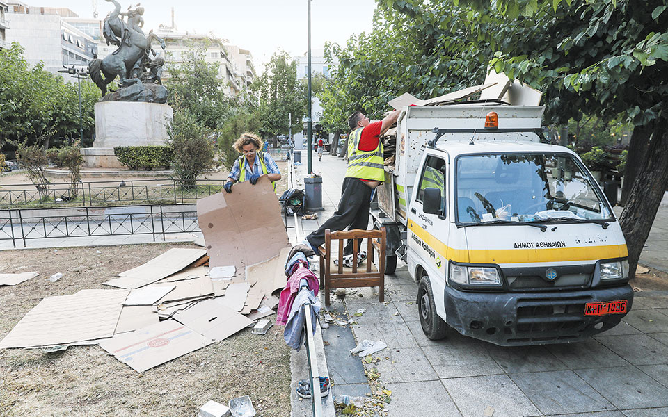 Συνεργείο καθαρισμού του Δήμου Αθηναίων στην πλατεία Βικτωρίας, αμέσως μετά την επιχείρηση μεταφοράς των προσφύγων (φωτ. INTIME NEWS)
