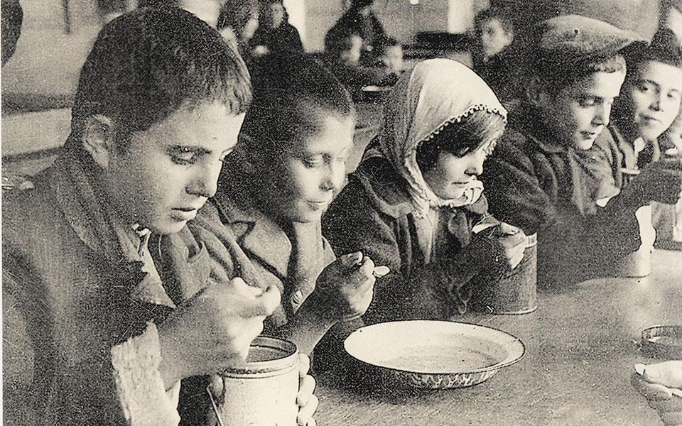 «Μαύρο λεύκωμα». Το εξέδωσε (χειροποίητο) η Βούλα Παπαϊωάννου το 1943 με φωτογραφίες από την έναρξη του πολέμου των νικών και των ηρώων και κατόπιν από την κατοχική ζωή εν τάφω του άμαχου πληθυσμού της Αθήνας με τον λιμό του φοβερού χειμώνα 1941-42. Τότε που τα κάρα αγκομαχώντας μετέφεραν σκελετωμένους νεκρούς, ομαδικοί τάφοι ανοίγονταν, σκιές ζωντανών ακροβατούσαν βαριανασαίνοντας, ψάχνοντας στα σκουπίδια ψίχουλα απαντοχής, άλλοι δίπλα τους σωριάζονταν με σιωπή. Επάνω, συσσίτιο παιδιών τους επόμενους μήνες, η γενιά των πατεράδων και παππούδων μας που διά πυρός και σιδήρου, βγαίνοντας όρθιοι από μυλόπετρες αλυσίδας πολυαίμακτων χρόνων ξανάχτισαν την Ελλάδα (φωτογραφικό αρχείο Μουσείου Μπενάκη).