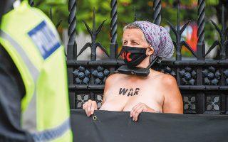 Γυμνόστηθη ακτιβίστρια... κλειδωμένη στα κάγκελα του Κοινοβουλίου (φωτ. A.P.).