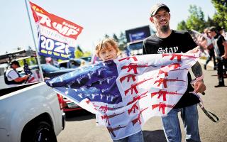 Aμαρτίες γονέων... Πιτσιρικάς συμμετέχει στη διαδήλωση υποστηρικτών του Τραμπ στο Σάλεμ, κρατώντας εκδοχή της αμερικανικής σημαίας με όπλα. (Φωτ. REUTERS / CARLOS BARRIA)