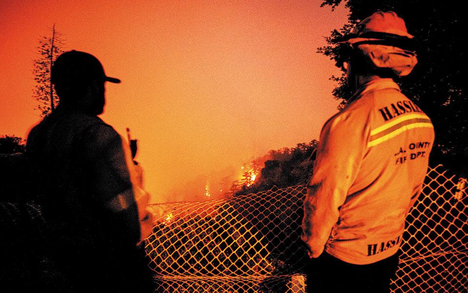Πυροσβέστες κοιτάζουν άπραγοι μία από τις πυρκαγιές που κατακαίνε την Καλιφόρνια. Οι φωτιές στην πολιτεία έχουν κάνει μέχρι στιγμής στάχτη περίπου 13.000 τ. χλμ. και εξακολουθούν να μαίνονται (φωτ. EPA).