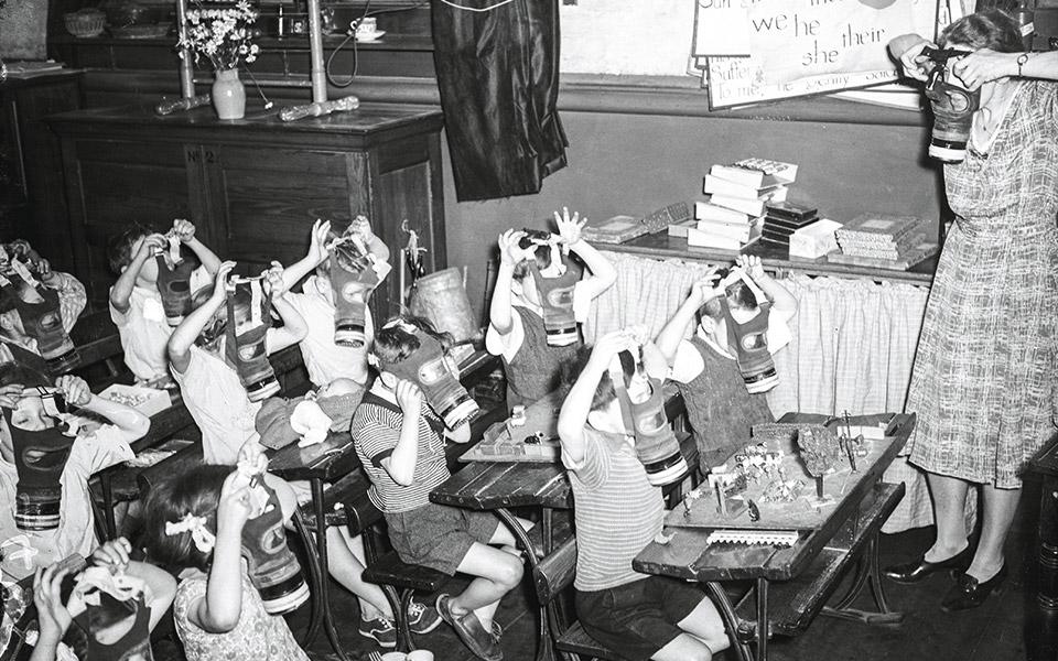 Δασκάλα δείχνει σε μαθητές Δημοτικού πώς να χρησιμοποιούν τις μάσκες αερίου, Λονδίνο, 1941. © GETTY IMAGES/IDEAL IMAGE