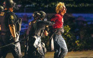 Αστυνομικοί συλλαμβάνουν νεαρό Αμερικανό στο Πόρτλαντ, κατά τη διάρκεια των ταραχών του Σαββάτου (φωτ. A.P.).