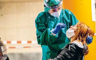 Υγειονομική υπάλληλος συλλέγει δείγμα για τεστ COVID-19 από μια γυναίκα, σε υπόγειο πάρκινγκ νοσοκομείου, στη Λιέγη του Βελγίου (φωτ. A.P.).
