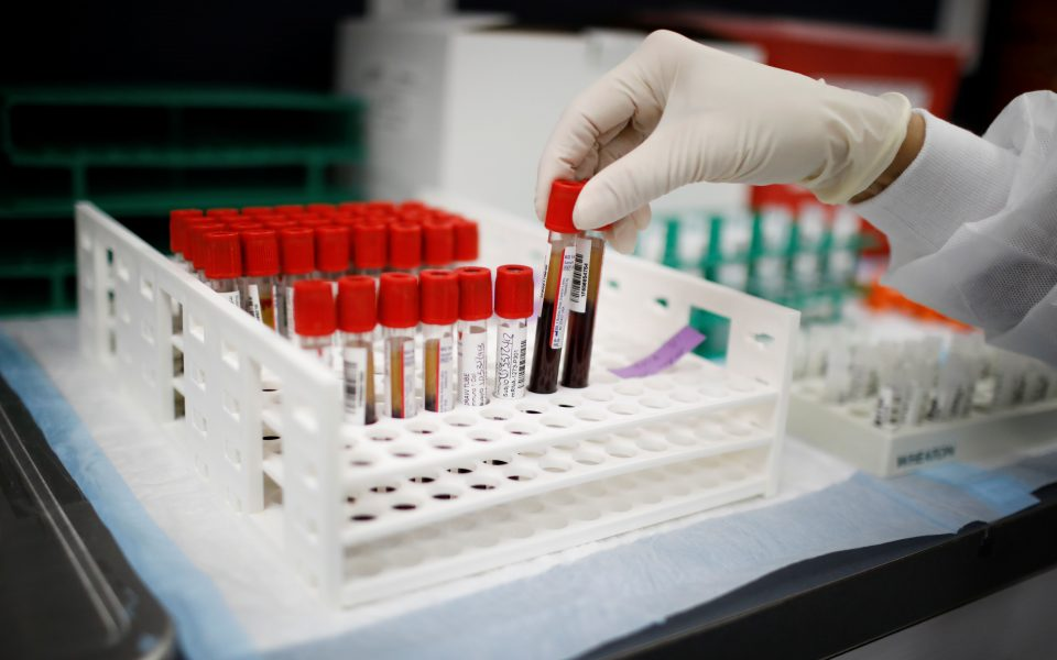 A health worker takes test tubes with plasma and blood samples after a separation process in a centrifuge during a coronavirus disease (COVID-19) vaccination study at the Research Centers of America, in Hollywood, Florida, U.S., September 24, 2020. REUTERS/Marco Bello