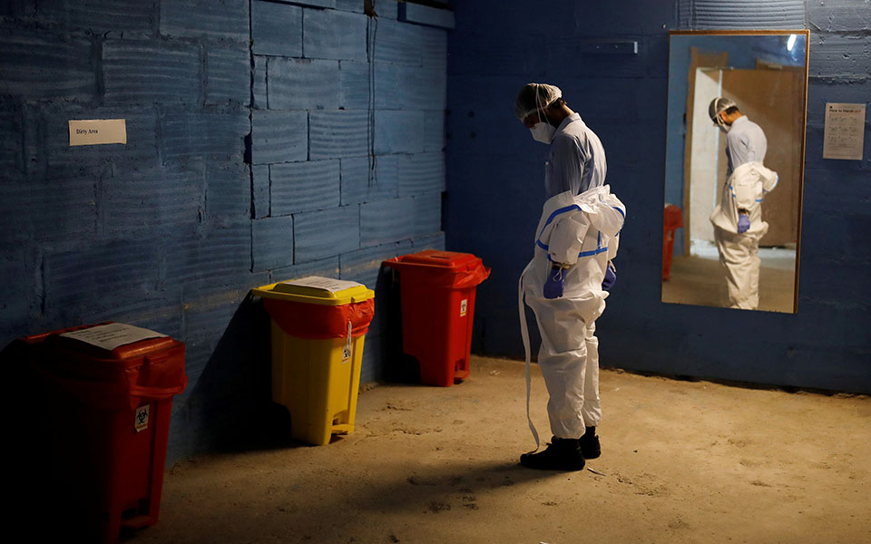 A medical worker takes off his personal protective equipment (PPE) as he leaves after his shift at the Yatharth Hospital in Noida, on the outskirts of New Delhi, India, September 15, 2020. Picture taken September 15, 2020. REUTERS/Adnan Abidi