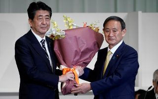 Japan's Prime Minister Shinzo Abe presents Chief Cabinet Secretary Yoshihide Suga with flowers after he was elected as new head of the ruling party at the Liberal Democratic Party's (LDP) leadership election in Tokyo, Japan September 14, 2020. Eugene Hoshiko/Pool via REUTERS