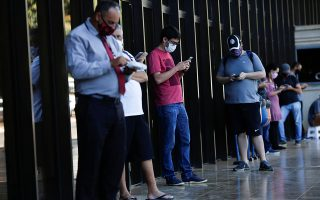 People wearing protective masks wait in line to change the 200 hundred reais note after Brazil's Central Bank issues the new note in Brasilia, Brazil September 2, 2020. REUTERS/Adriano Machado
