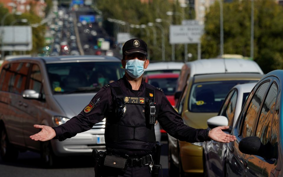 A Spanish National Police officer wearing a protective mask gestures at a traffic checkpoint during a partial lockdown amid the outbreak of the coronavirus disease (COVID-19), in Madrid, Spain October 9, 2020. REUTERS/Juan Medina