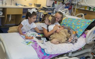In this photo provided by Johns Hopkins All Children's Hospital, Lauren Glynn is visited by friends Chloe Grimes, Avalynn Luciano and McKinley Moore in her room at the hospital in St. Petersburg, Fla., Aug. 28, 2019. The girls, who were diagnosed with cancer in 2016 and became fast friends while undergoing treatment, reunite every year. (Allyn DiVito/John Hopkins All Children's Hospital via AP)