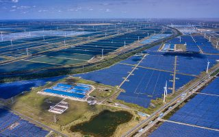 epa08743694 A photo made with a drone shows general view of the solar panels and wind turbines of Wind, Solar and Fishing Base in Dongtai near Yancheng, Jiangsu province, China, 14 October 2020. The largest integrated power station of
