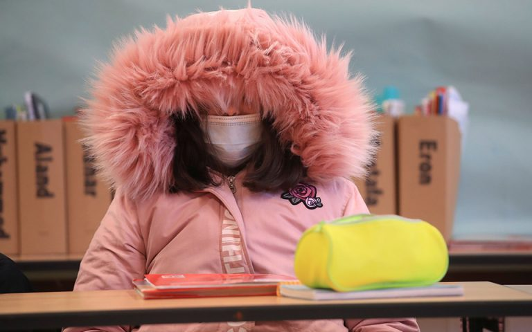 Schoolgirl of Freiherr-vom-Stein secondary school in the North Rhine-Westphalian city Bonn wears a winter outfit against the cold as school resumes with open windows and protective masks against the spread of COVID-19 following the autumn holidays in Germany, October 26, 2020. REUTERS/Wolfgang Rattay