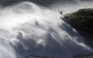 A surfer raises his arms as he exits a wave during a tow surfing session at Praia do Norte or North Beach in Nazare, Portugal, Thursday, Oct. 29, 2020. A big swell generated earlier in the week by Hurricane Epsilon in the North Atlantic, reached the Portuguese west coast drawing big wave surfers to Nazare. (AP Photo/Pedro Rocha)