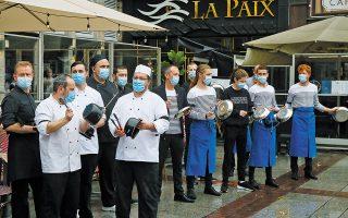 Στο Παρίσι, επιχειρηματίες του τομέα της εστίασης και το προσωπικό τους στάθηκαν έξω από τα καταστήματά τους, φορώντας μαύρα περιβραχιόνια, χτυπώντας κατσαρόλες και ζητώντας από τη γαλλική κυβέρνηση να μην αυξήσει τα περιοριστικά μέτρα (φωτ. A.P.).