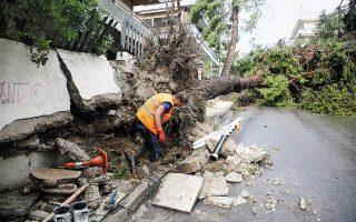 Χθες, περίπου 150 δέντρα έπεσαν πάνω σε αυτοκίνητα και κτίρια, κολόνες της ΔΕΗ έπεσαν, στέγες ξηλώθηκαν, ενώ οι δρόμοι γέμισαν νερά. Από τις πτώσεις αντικειμένων προκλήθηκαν σοβαρά κυκλοφοριακά προβλήματα, ενώ υπήρχαν διακοπές σε ηλεκτροδότηση και υδροδότηση (φωτ. EPA/ALEXANDROS VLACHOS).