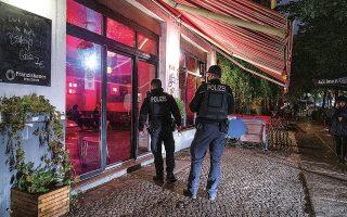 Αστυνομικοί κάνουν έλεγχο για την τήρηση των μέτρων σε μπαρ στο Φρίντριχσχαϊν, στο Βερολίνο. Μάλιστα την Τετάρτη, η καγκελάριος Αγκελα Μέρκελ ανήγγειλε την αυστηροποίησή τους, επισημαίνοντας πως ό,τι κάνουμε τώρα θα είναι καθοριστικό για το μέλλον (φωτ. Christophe Gateau/dpa via A.P.).