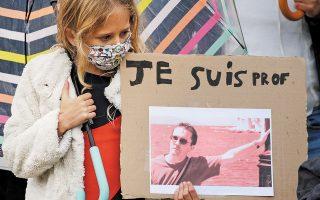 Νεαρή με φωτογραφία του δολοφονημένου καθηγητή Σαμιέλ Πατί, σε μια από τις μαζικές διαδηλώσεις υποστήριξης στις αξίες της γαλλικής δημοκρατίας.  (Φωτ. REUTERS / Pascal Rossignol)