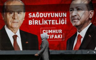 A woman walks past a banner for the upcoming local elections in Ankara, Turkey, March 27, 2019. Banner with pictures of Turkish President Tayyip Erdogan and Devlet Bahceli, leader of Nationalist Movement Party (MHP), reads: