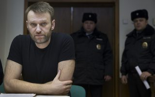 Russian opposition activist Alexei Navalny, left, sits in a court room in Moscow, Russia, Friday, Feb. 27, 2015. Navalny was detained earlier this month for 15 days for distributing leaflets for an anti-government march, which he will miss if he remains in prison. (AP Photo/Pavel Golovkin)