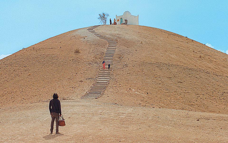 Ενας άνδρας επιστρέφει έπειτα από χρόνια στην κορυφή του λόφου, όπου κάποτε έθαψε τη λεία μιας μεγάλης ληστείας. Διαπιστώνει ωστόσο πως εκεί έχει χτιστεί το μαυσωλείο του Αγνώστου Αγίου, ενώ στα πόδια του λόφου έχει αναπτυχθεί ολόκληρος οικισμός.