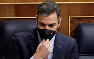 Spain's Prime Minister Pedro Sanchez adjusts his protective face mask at the start of a motion of no confidence against his government session at Parliament in Madrid, Spain, October 21, 2020. Manu Fernandez/Pool via REUTERS
