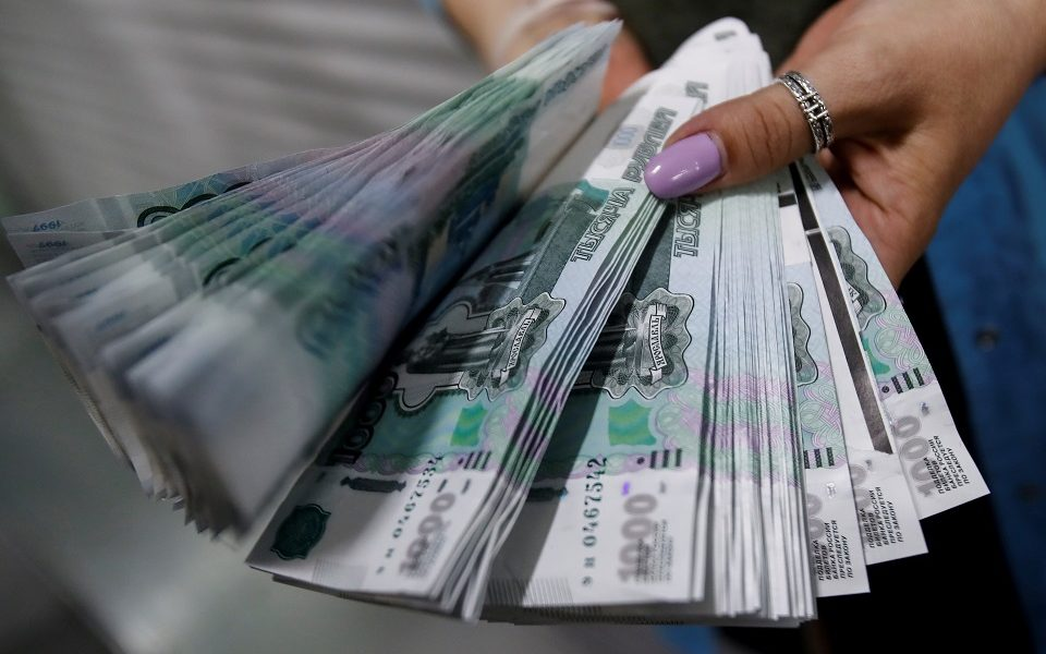 FILE PHOTO: An employee holds 1,000 Russian Roubles notes at Goznak printing factory in Moscow, Russia July 11, 2019. REUTERS/Maxim Shemetov/File Photo