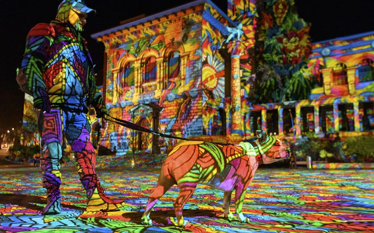 epa08838588 A person with a dog looks at the light projection 'Diving in the sea of colors' by the German light artist Daniel Margraf on the Palais de Rumine in the Place de la Riponne ahead of the Festival Lausanne Lumieres (Lausanne Light Festival), in Lausanne, Switzerland, 23 November 2020 (issued 24 November 2020). Eight projections on different buildings aiming to showcase the city of Lausanne under a new light will be on shows during the festival that runs from 24 November to 24 December 2020.  EPA/LAURENT GILLIERON